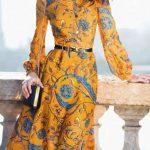 Belle robe maxi longueur ceinturee avec manche longue imprime fleur et arabesques bleu sur fond jaune orange